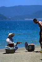 White man buying fresh lobster from beach vendor, Nha Trang, Vietnam