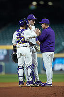 LSU Tigers pitching coach Alan Dunn has a meeting on the mound with starting pitcher Cole Henry (18) and catcher Alex Milazzo (20) during the game against the Texas Longhorns in game three of the 2020 Shriners Hospitals for Children College Classic at Minute Maid Park on February 28, 2020 in Houston, Texas. The Tigers defeated the Longhorns 4-3. (Brian Westerholt/Four Seam Images)
