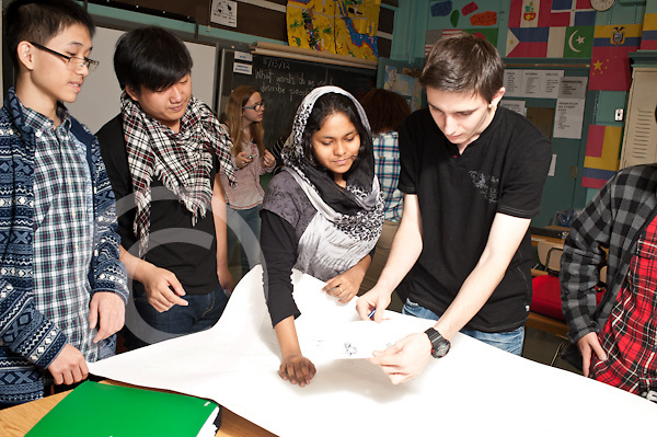 High school group of students planning poster on world peace and racial harmony working together