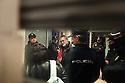El compañero de una activista la espera en la puerta del banco rodeado por policía nacional.
