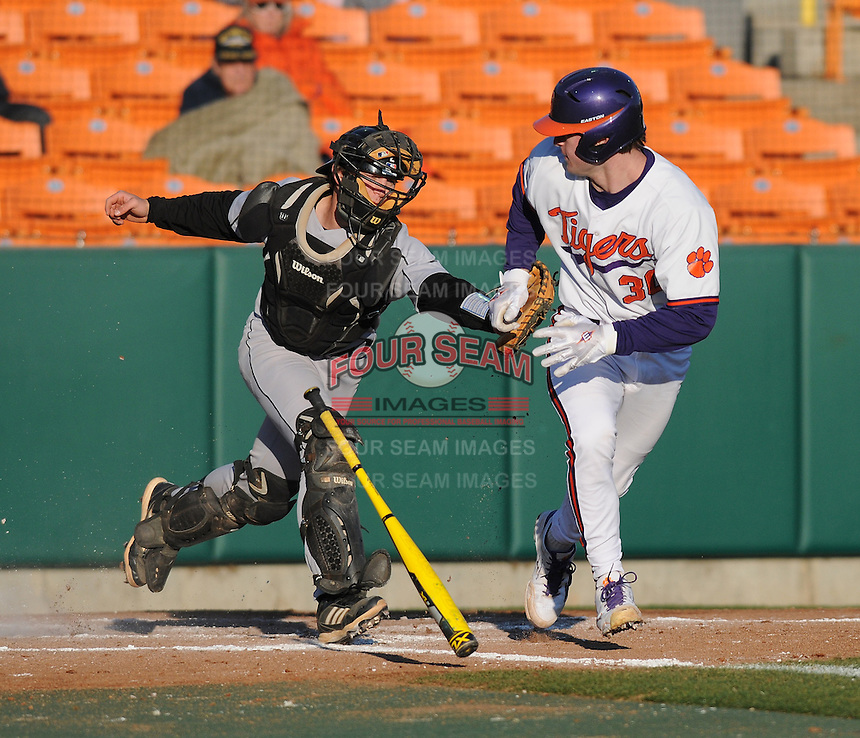 Catcher Garrett Boulware (30) of the Clemson Tigers is tagged out by catcher Luke Feisal (2) of the Wofford Terriers after striking out in the fifth inning of a game on Wednesday, March 6, 2013, at Doug Kingsmore Stadium in Clemson, South Carolina. Clemson won, 9-2. (Tom Priddy/Four Seam Images)