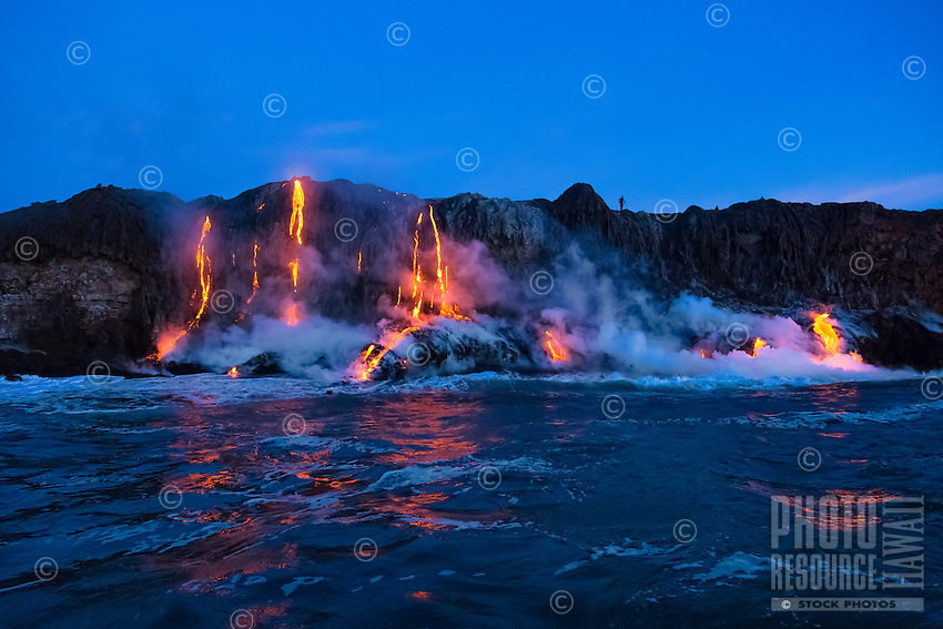 At dawn on the 30th anniversary of Kilauea's eruption, lava enthusiasts view lava flowing into the ocean along the border of Hawai'i Volcanoes National Park on the Big Island.