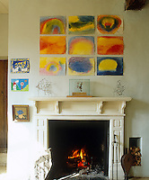 Detail of the children's paintings are displayed on the wall above the fireplace in the kitchen