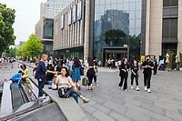 Suzhou, Jiangsu, China.  Pedestrian Street Traffic outside Entrance to a Shopping Mall.