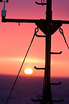 The sunsets in the Arctic on the West coast of Greenland. In the foreground a ship mast.