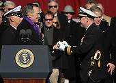 Norfolk, VA - January 10, 2009 -- Lieutenant Commander George Brickhouse, assigned to the aircraft carrier USS George H.W. Bush (CVN 77) accepts a long glass symbolizing the setting of the first watch from former United States President George H.W. Bush during the ship?s commissioning ceremony at Naval Station Norfolk, Va. Bush delivered the keynote address at the commissioning. The Navy's newest, and final, Nimitz-class aircraft carrier is named after the World War II naval aviator and 41st president of the United States. .Credit: Micah P. Blechner - U.S. Navy via CNP