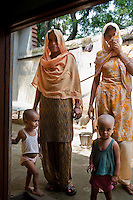 "Shashi Devi (aged 28, left) and her brother-in-law's wife Monika Devi (22, right) stand in their house in the village of Shahpurjat, Ghaziabad, Uttar Pradesh, India. While Shashi had a tubectomy done after having 2 sons, Monika is still trying for a son after having 2 daughters. Shashi did the operation because she wanted to ""give her 2 children the best and inflation will make things difficult"", and she believes that a ""small family = happy family"". She has been pushing Monika to get her husband to do an NSV so that Monika's life is not endangered since her previous pregnancies have been complicated. Photo by Suzanne Lee / Panos London"