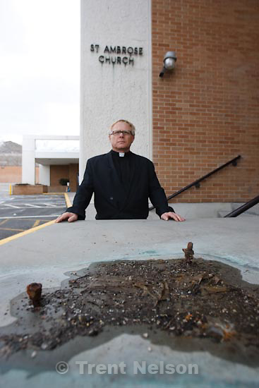 Trent Nelson  |  The Salt Lake Tribune.Salt Lake City - Father Andrzej Skrzypiec stands near two rusted bolts, all that is left of a seven foot tall statue of Saint Ambrose that was stolen over the weekend from the Saint Ambrose Catholic Church. Sunday, March 14, 2010.