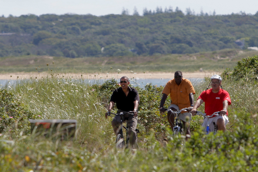 President Barack Obama, left, rides his bike with his family and friends including Dr. Eric Whitaker, right, while on vacation on Martha's Vineyard on Lobsterville Beach in Aquinnah, Mass....
