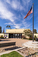 The main entrance to the lovely municipal auditorium at South Gate Park framed with the wind-blown flag and streaks of clouds in a blue sky.