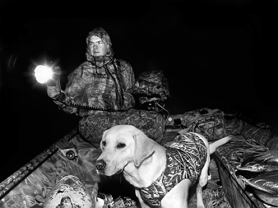 "Hayes Hudson, a well known local hunter, both for his sportsmanship and skill, navigates the river before dawn with his yellow labrador retriever, ""Regen"", on the opening day of duck hunting season in Horry County, SC."
