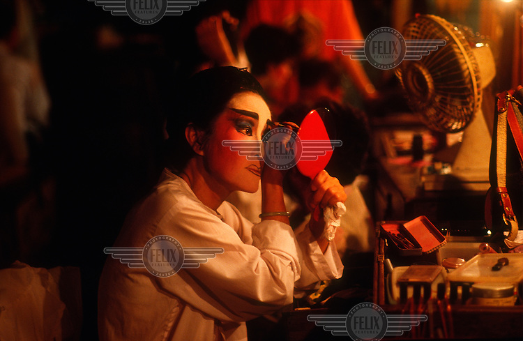 Woman applying her make-up before performing in a Chinese Opera during Chinese New Year celebrations in Georgetown.