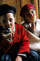 Two little girls dressed in berets and warm winter jackets sit together eating a toffee apple and a slice of bread covered in jam