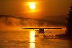 Sunrise silhouette of a floatplane on Homer Alaska's Beluga Lake.