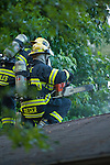Emergency response: Firefighters attack a house fire from the roof with chainsaw and air tanks deployed.