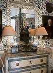 A detail of a traditional, blue bedroom with pattern wallpaper, decorative painted chest of drawers, ornate mirror, pair of lamps