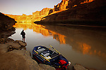 A young man enjoys first light on the Colorado River in Canyonlands National Park, Utah