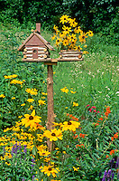 Unique log cabin bird house front view with planter made of rudibeckia, summer garden, Midwest USA