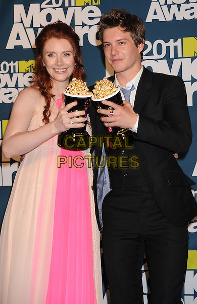 Bryce Dallas Howard, Xavier Samuel.in the Press Room at the 2011 MTV Movie Awards at Universal Studios' Gibson Amphitheatre in Universal City, California, USA, June 5th 2011.  .pressroom half length pregnant pink beige dress award trophies suit tie .CAP/ROT/TM.©TM/Roth Stock/Capital Pictures