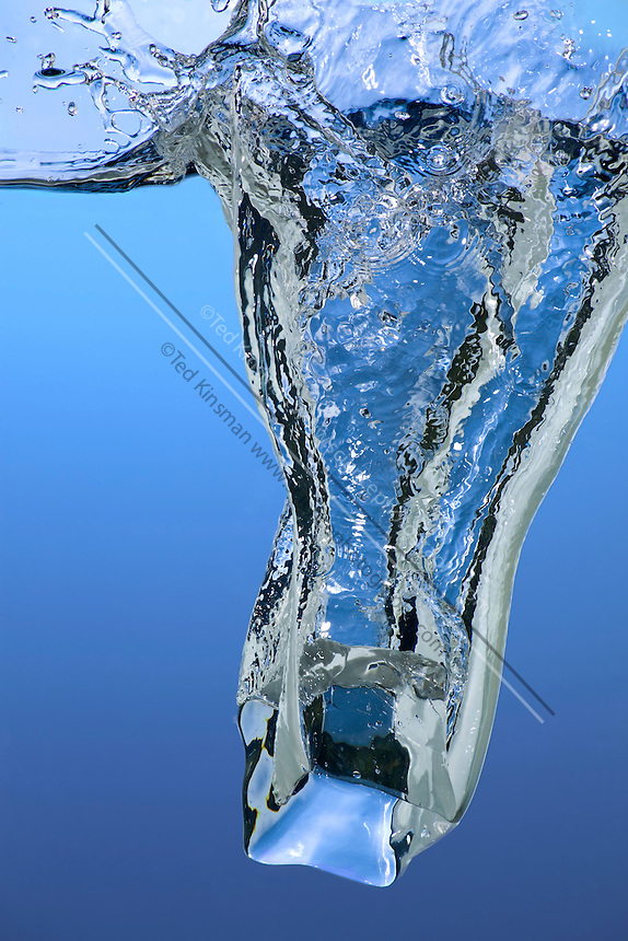 An ice cube is dropped in water, creating a splash.