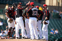 Rochester Red Wings manager Mike Quade (8) signals for a pitching change flanked by Eric Fryer, Reynaldo Rodriguez (23) and James Beresford during a game against the Norfolk Tides on May 3, 2015 at Frontier Field in Rochester, New York.  Rochester defeated Norfolk 7-3.  (Mike Janes/Four Seam Images)