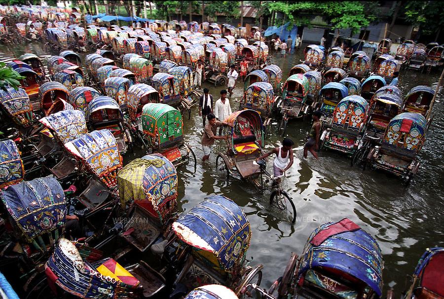 2004. Rickshaws are chained in a garage since all the roads are flooded in Dhaka. Des rickshaws sont attachés dans un garage car les routes sont impraticables à cause des inondations à Dacca.