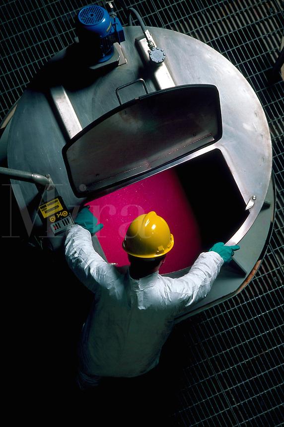 Overhead shot of paper plant worker looking into vat of dye.
