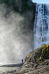 Man fishing from rocks at the base of Montmorency Falls, Quebec Canada