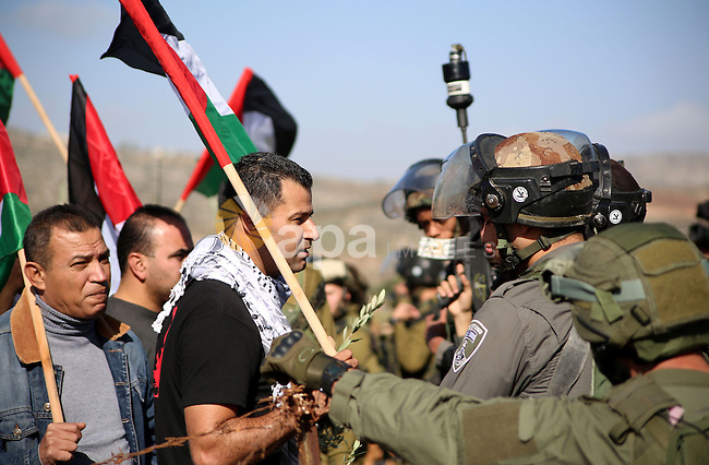 A Palestinian man argues with An Israeli guard during a demonstration intended to plant 300 olive trees in the village of Turmus Aya near Ramallah, in the Isareli-occupied West Bank, on December 10, 2014. Ziad Abu Ein, who was in charge of the issue of Israeli settlements for the Palestinian Authority, died after being beaten by Israeli forces during the protest march in the West Bank, medical and security sources said. Photo by Shadi Hatem