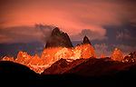Mt. Fitzroy, Argentina.  Early morning sunlight penetrates a partially clouded sky, illuminating the low hills surrounding the spire of Mount Fitzroy in alternating bands of light and shade.  The strength of this photograph is in the soft pastels of pink and blue in the early sky, contrasting with the warm golds of the illuminated hillside.