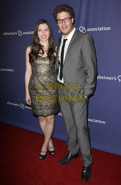 "LAUREN MILLER & SETH ROGEN.18Th Annual ""A Night at Sardi's"" Benefitting The Alzheimer's Association held At The Beverly Hilton Hotel, Beverly Hills, California, USA..March 18th, 2010.full length gold green dress grey gray suit black tie glasses couple beard facial hair stubble.CAP/ADM/KB.©Kevan Brooks/AdMedia/Capital Pictures."