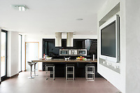 A large television screen is suspended from the ceiling of the spacious kitchen/living area of the large open-plan house