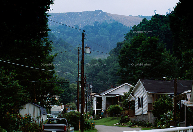 A road into a holler of homes reveals a rare view of a mountaintop removal mine that sits over the community.