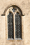 Building exterior medieval church architectural feature decorated glass window in stone wall, Inglesham, Wiltshire, England, UK
