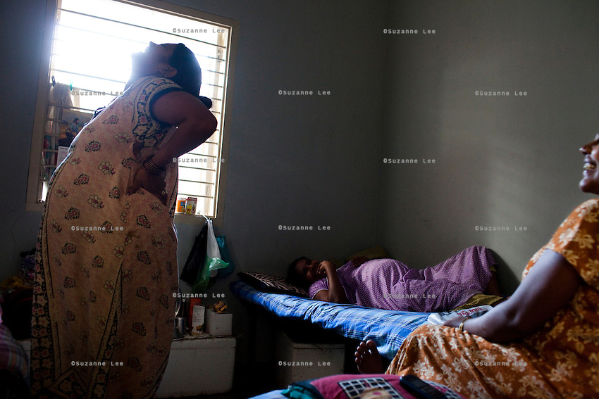 (L-R) Manjula Vinod Zala (27), Martha Sanjay Chauhan (purple) (35), and Haital Jagdishbhai Solanki, 24, (sister of Manjula Vinod Zala)...Women tell jokes and lounge around the surrogate house for their entire term of pregnancy while posters of babies and religious symbols adorn the walls together with calendars that they often use to count their days to the end of their terms. The women come to the house with just a small bag of clothes as everything else is provided for in the house...The Akanksha Infertility Clinic in Anand, Gujarat, India, is known internationally for its surrogacy program and currently has over a hundred surrogate mothers pregnant in their environmentally controlled surrogate houses.