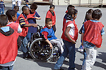Oakland CA Elementary school students giving support to boy in wheel chair, getting ready for casual basketball game  MR