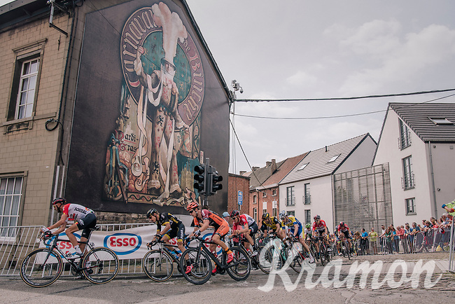 The 'Gilles de Binche' are traditional carnaval characters protected under UNESCO's cultural heritage and are the pride of the city. This mural serves as a salute to everybody entering the city.<br /> The peloton passes this mural 13 times today.<br /> <br /> Belgian National Championships 2018 (road) in Binche (224km)<br /> ©kramon