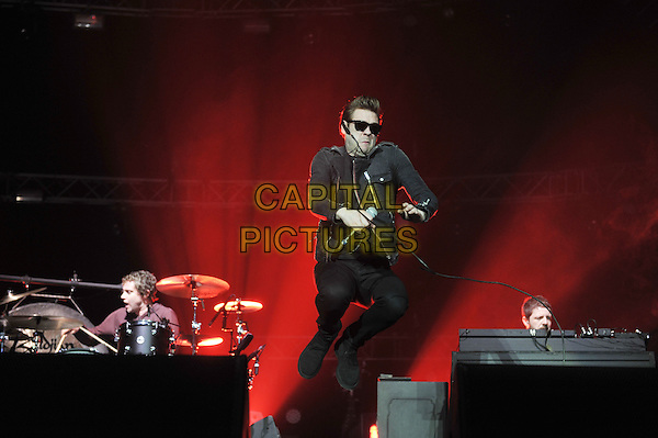 Tom Meighan.Kasabian performing at the o2 Arena, Greenwich, London, England..31st December 2011.in concert on stage live gig performance music full length black jacket sunglasses shades jump jumping  .CAP/MAR.© Martin Harris/Capital Pictures.