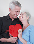 Smiling mature couple with heart shaped box