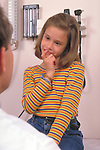 young girl listens to doctor during examination