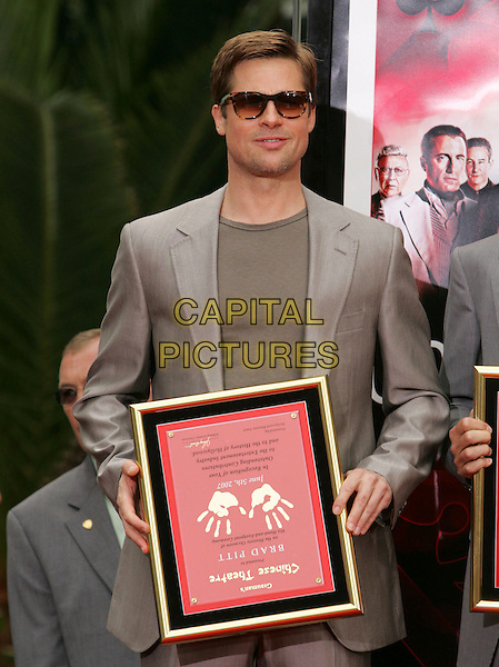BRAD PITT.At The Warner Brothers' Hand & Foot Print Ceremony for Ocean's Thirteen at The Grauman's Chinese Theatre in Hollywood, California, USA..June 5th, 2006.half length beige suit jacket plaque sunglasses shades funny upside down.CAP/DVS.©Debbie VanStory/Capital Pictures