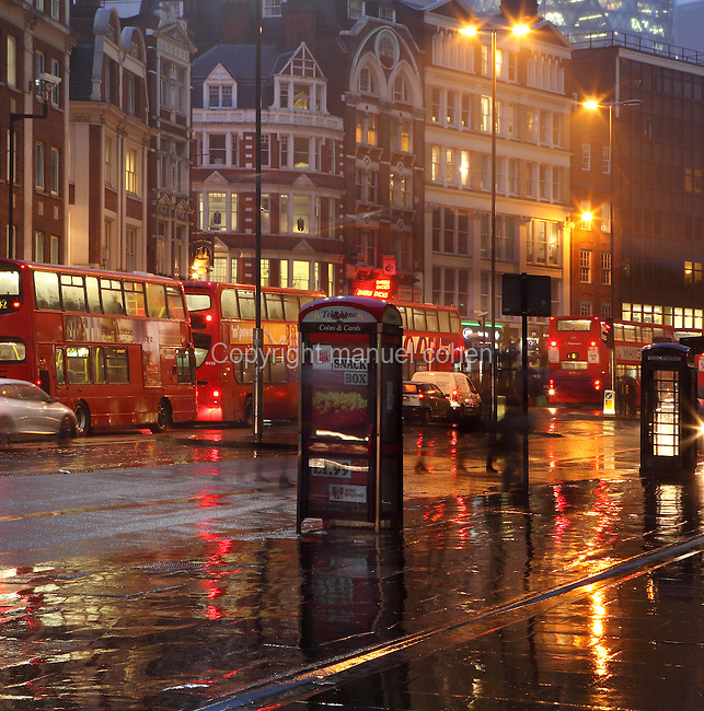 London rush hour, traffic jam with London buses waiting in line, at dusk, beneath a rainy sky, UK. Picture by Manuel Cohen