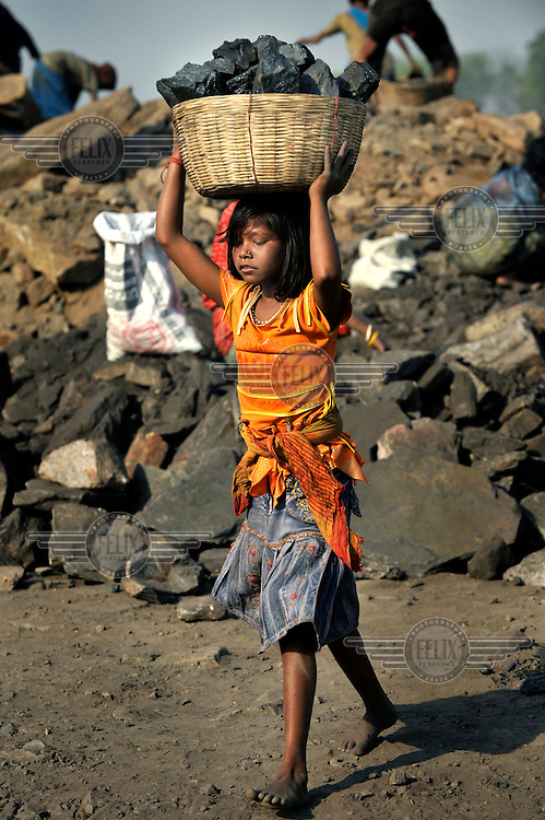 A girl carries a basket of coal on her head. The coal is illegally collected from rubble at the edge of a massive open cast mine. Many villagers survive by selling coal that has been illegally collected.