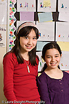 Elementary school Grade 5 closeup portrait of two girls friends differing heights at same age vertical
