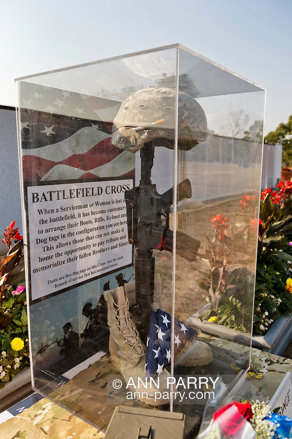 """East Meadow, New York, U.S. 11th September 2013. The Battlefield Cross display is in front of the Global War on Terror """"Wall of Remembrance"""" a traveling memorial on display in New York for the first time, at Eisenhower Park on the 12th Anniversary of the terrorist attacks of 9/11. The unique 94 feet long by 6 feet high wall has, on one side, almost 11,000 names of those lost on September 11th 2001, along with heroes and veterans who lost their lives defending freedom of Americans over past 30 years."""