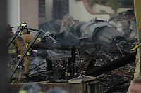 Monday December 8, 2008:  University City, San Diego California.  Rescue workers work at the scene where a military jet crashed into a residential home killing at least 2 civilians.  At approximately 11:59am a USMC F-18 fighter jet encountered trouble over this residential area of the city and the pilot ejected leaving his aircraft to crash into a residential neighborhood.