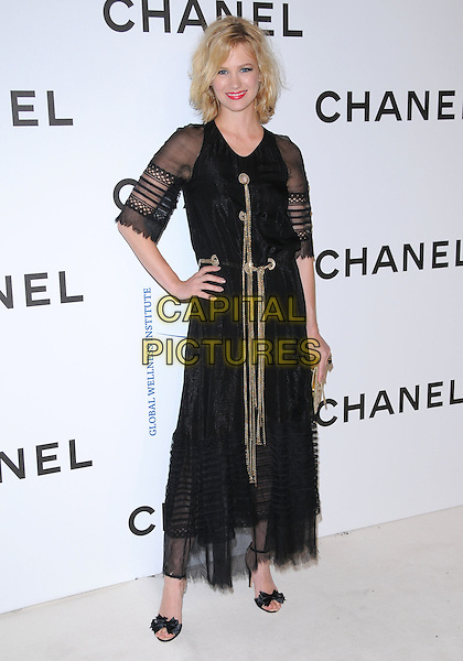 JANUARY JONES.at The Chanel Boutique Opening on Robertson Blvd. in Beverly Hills, California, USA, May 29 2008..full length dress sheer sleeves shoes black sandals bows satin ankle strap feet gold tassels clutch bag purse hand on hip .CAP/DVS.©Debbie VanStory/Capital Pictures