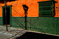 A shadow of a decorative street lamp falls across the facade of a brightly painted colonial house in Sonsón, a village in the coffee region (Zona cafetera) of Colombia, 15 October 2019.