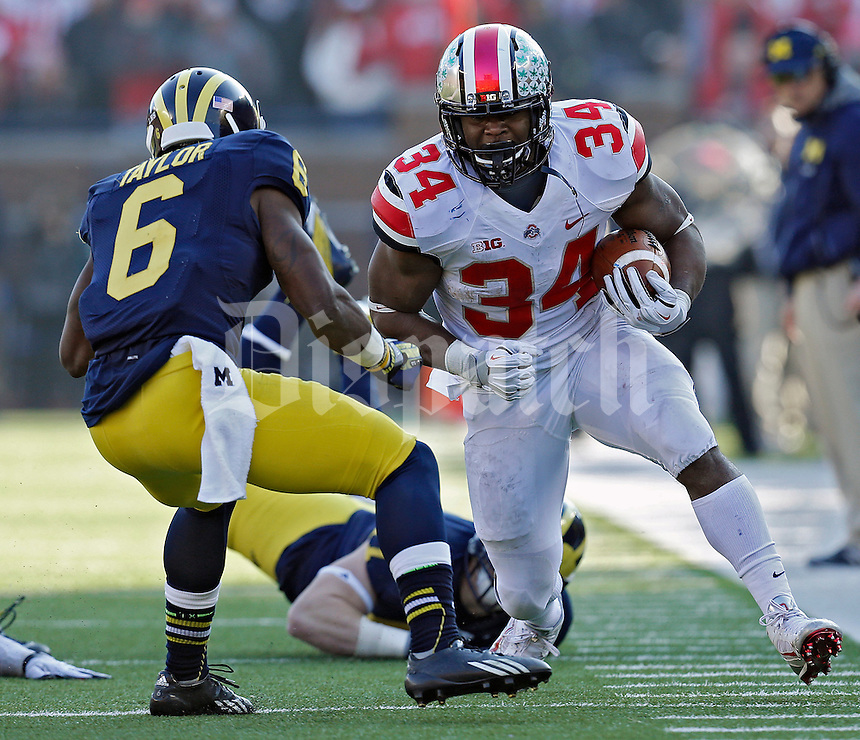 Ohio State Buckeyes running back Carlos Hyde (34) tries to get past Michigan Wolverines defensive back Raymon Taylor (6) in the 3rd quarter of their college football game at Michigan Stadium in Ann Arbor, Michigan on November 30, 2013.  (Dispatch photo by Kyle Robertson)