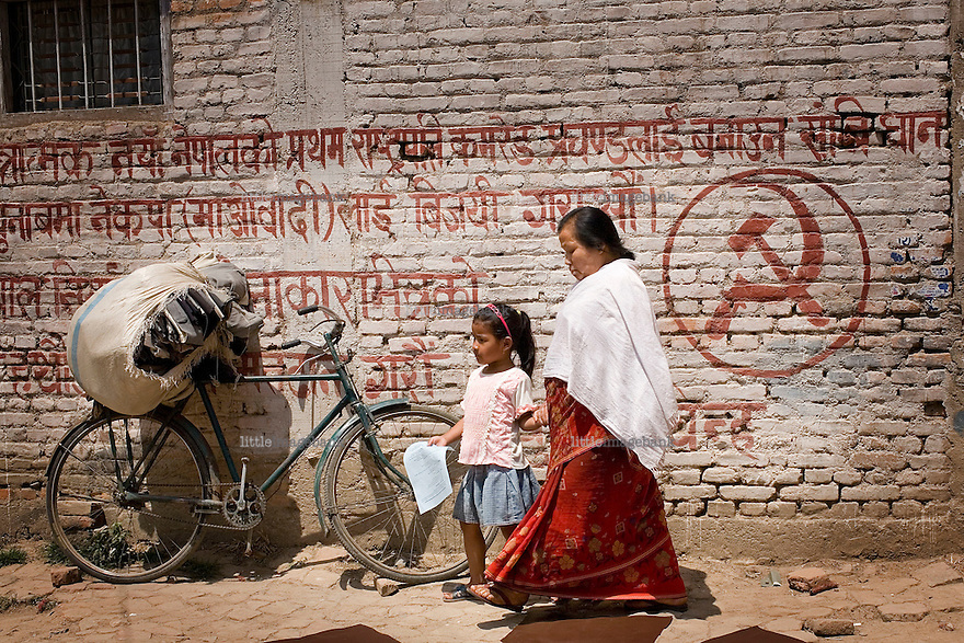 A woman and a child passes maoist propaganda in Kathmandu. The policeforces geared up for massive riots, but none erupted. April 10th 2008 the historic Consistuent assembly elections took place in Nepal, putting an end to a centuries of monarchy. The assembly will form a new constitution and abolish the monarchy and King Gyanendras rule. The big question remains if the new maoist led government will be a positive or a negative factor in a country that recently emerged from a decade of civilwar. Photo: Christopher Olssøn.